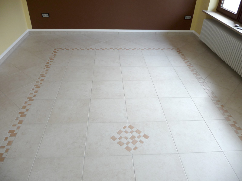 Bodenbelag aus Feinsteinzeugfliesen mit Mosaikfries und Einleger - leerer Raum