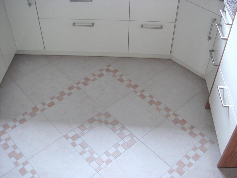 Bodenbelag aus Feinsteinzeugfliesen mit Mosaikfries und Einleger - mit Schränken